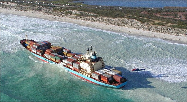 A giant cargo ship run aground on a beach, risking the loss of shipping containers overboard.