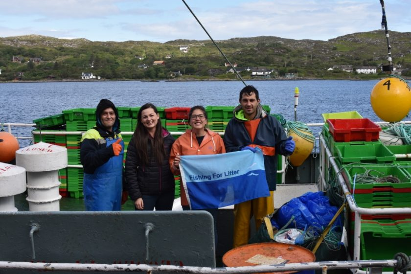 Fishermen and KIMO representatives hold the KIMO flag on board one of the 320 Fishing for Litter vessels around the UK.