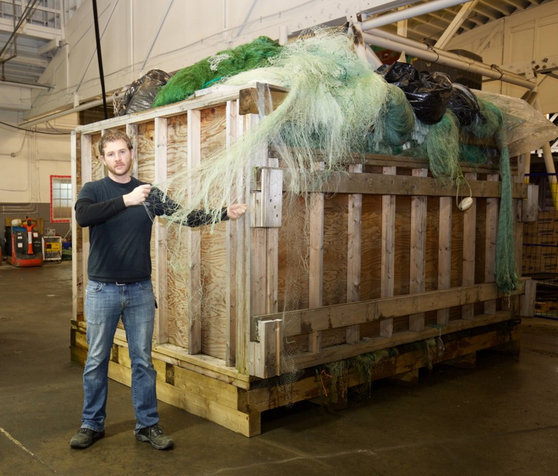 A man standing next to a large container full of recovered ghost gear.
