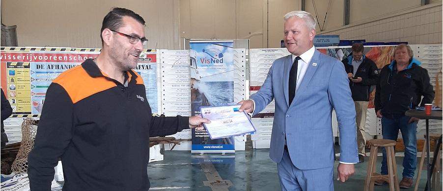 Alderman Kees Visser presenting a Fishing for Litter certificate to a fisherman in Den Helder, the Netherlands.