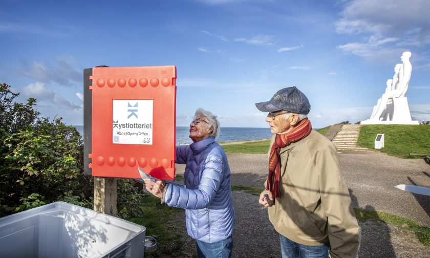 Two visitors to a beach in Esjberg, Denmark take part in the 'Coastal Lottery' for clean beaches.
