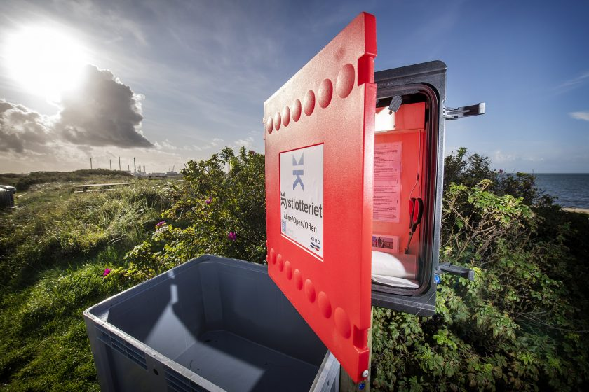 A red 'Coastal Lottery' collection point on a beach in Esbjerg, Denmark.