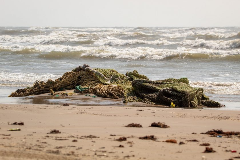 A discarded fishing net - known as 'ghost gear' - on a beach with the sea in the background.