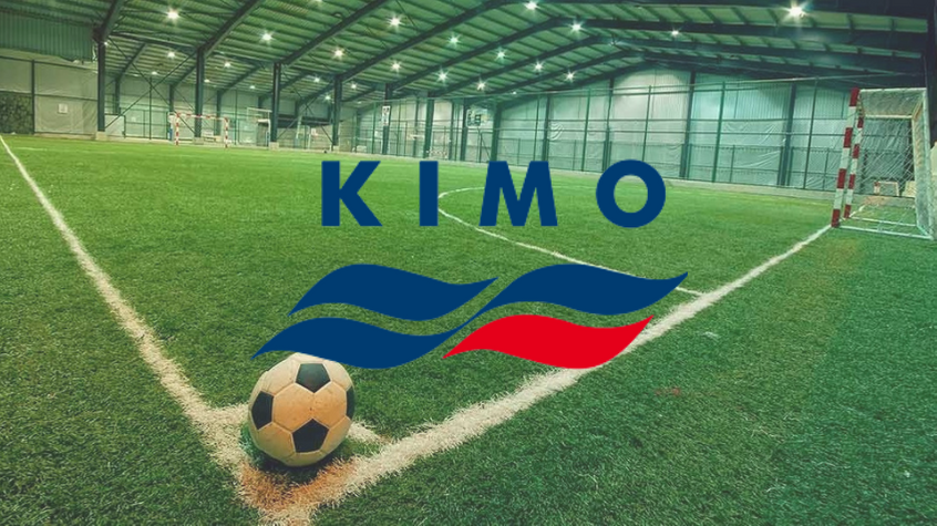 A football in the corner of an artificial sports pitch, with KIMO logo.