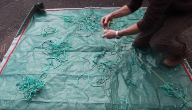 A fisherman collecting net cuttings on a tarpaulin.