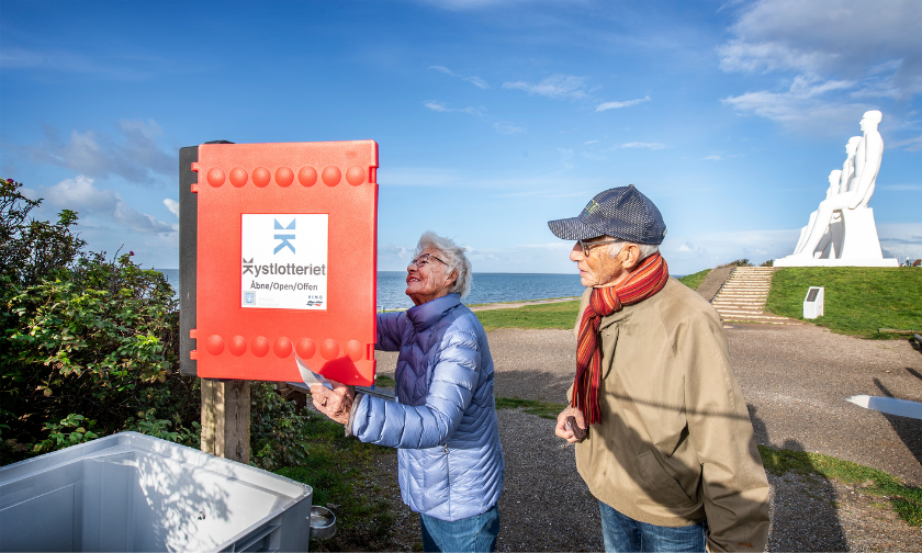 Visitors to the Danish coast open an information box to take part in the Coastal Lottery.